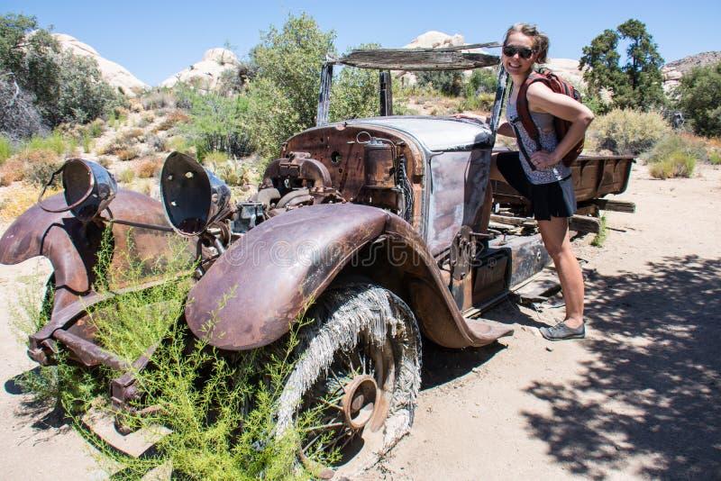 逗人喜爱的妇女徒步旅行者乘生锈和腐朽在约书亚树国家公园沙漠的一辆被放弃的古板的汽车摆在  免版税库存图片