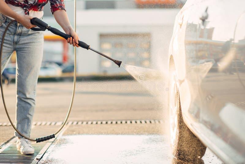 逗人喜爱的妇女清洗车轮与水枪 免版税图库摄影