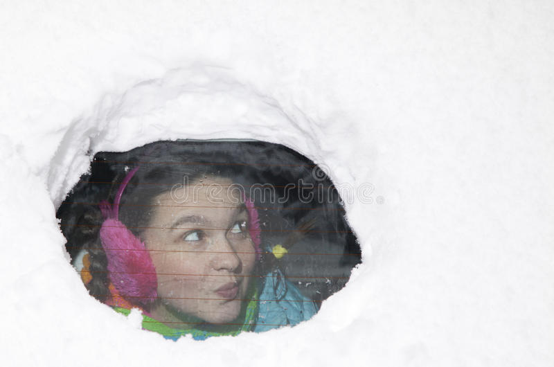 逗人喜爱的妇女驱动器使查找从一个多雪的车窗的后面惊奇 免版税图库摄影