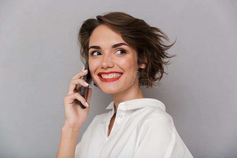 逗人喜爱的妇女20s照片微笑和发表演讲关于手机,是 库存照片