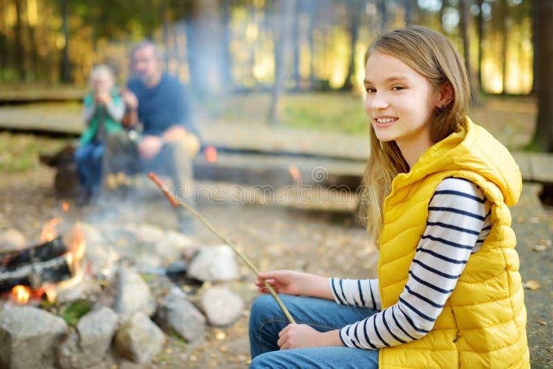 逗人喜爱的妹和他们的父亲烤蛋白软糖在棍子在篝火 孩子获得乐趣在阵营火 野营与 库存照片