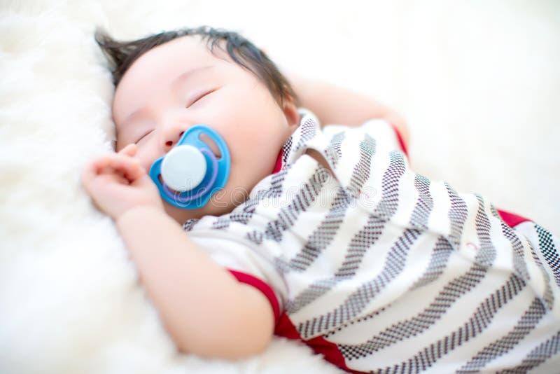 逗人喜爱的婴孩在一张软的白色地毯吮安慰者并且睡觉 可爱的婴孩在一张软的白色地毯躺下 免版税库存照片