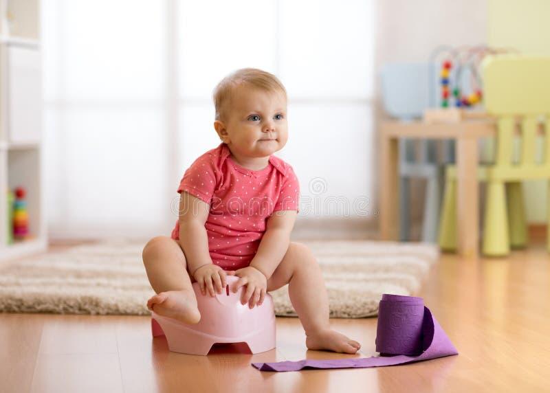 逗人喜爱的婴孩坐有卫生纸卷的便壶 免版税库存照片