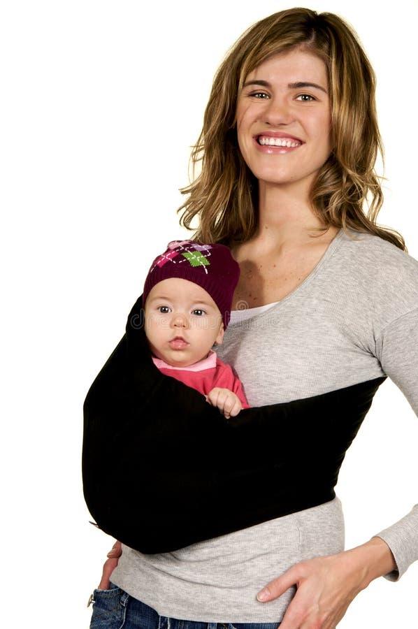 逗人喜爱的婴孩她的妈妈吊索 免版税库存图片