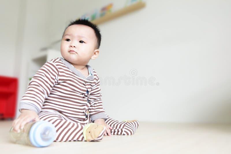 逗人喜爱的婴孩查找留下并且采取他的哺乳瓶 免版税图库摄影