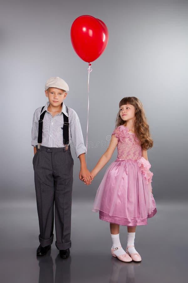 逗人喜爱的子项走与一个红色气球 免版税库存照片