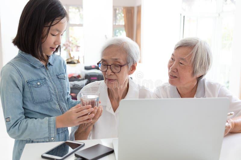 逗人喜爱的孙女给的或服务的水祖母喝,愉快的两个前辈亚裔妇女、姐妹或者朋友的 免版税库存照片