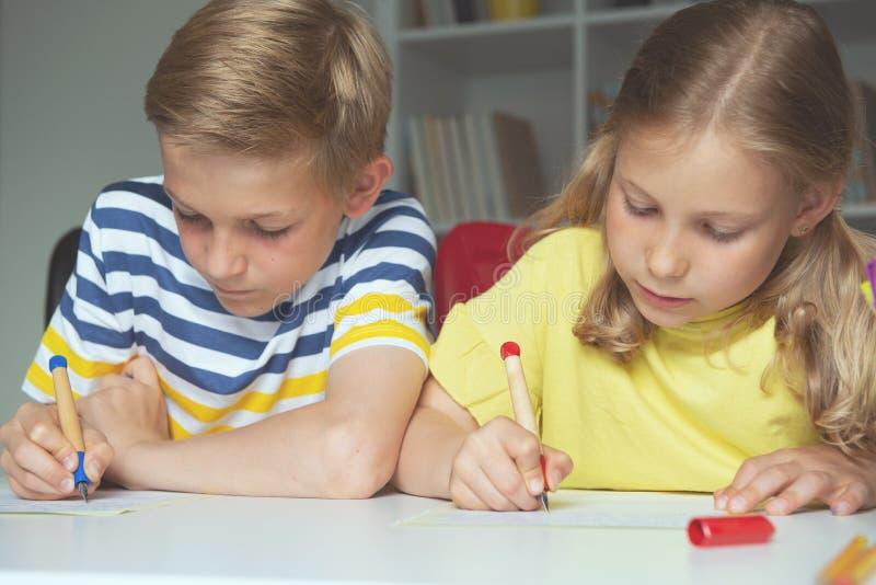 逗人喜爱的学童是回来了到学校和学会在桌上在教室 库存图片