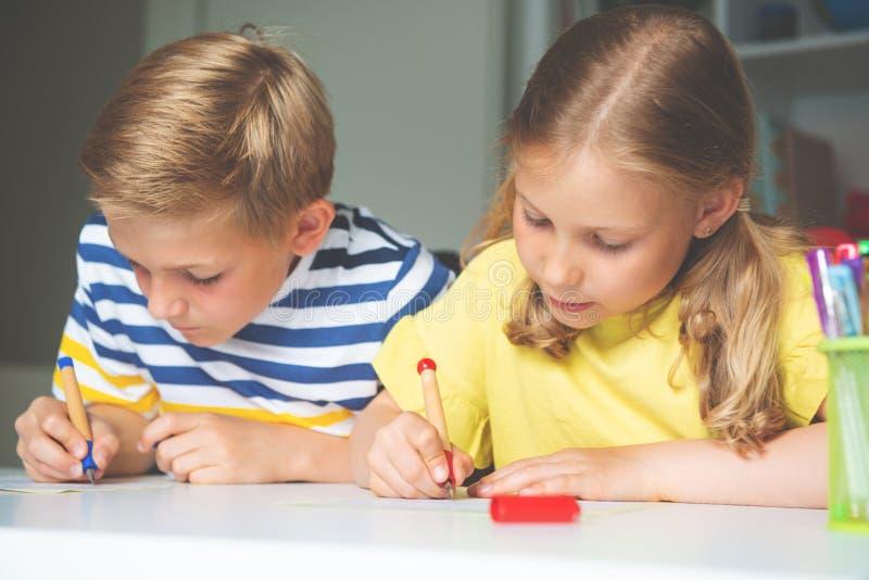 逗人喜爱的学童是回来了到学校和学会在桌上在教室 免版税库存图片