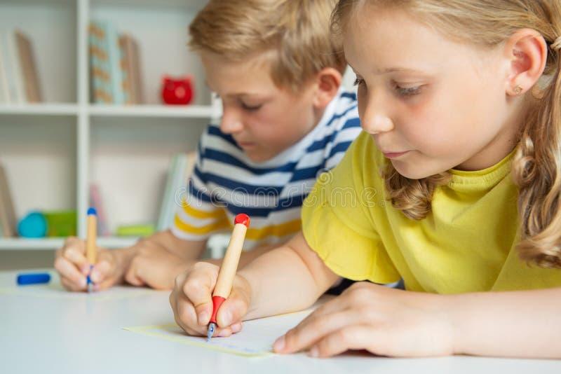 逗人喜爱的学童是回来了到学校和学会在桌上在教室 免版税图库摄影