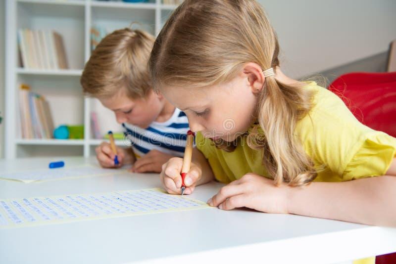 逗人喜爱的学童是回来了到学校和学会在桌上在教室 免版税库存照片