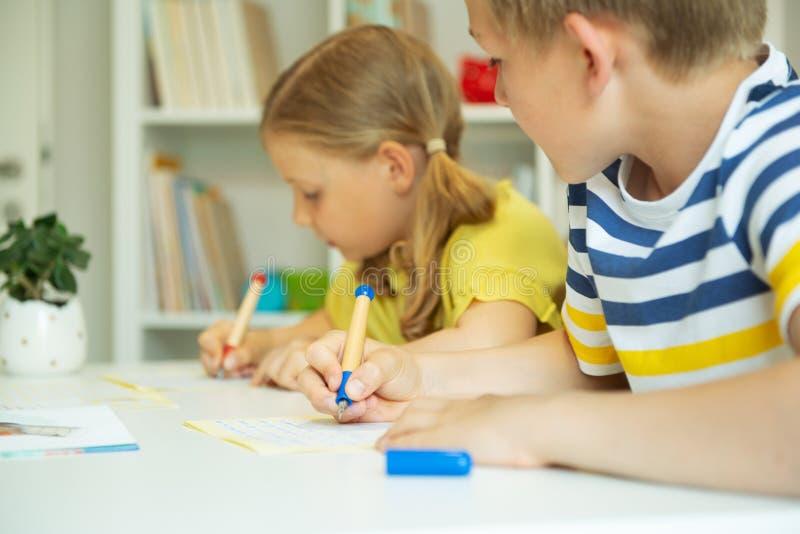 逗人喜爱的学童是回来了到学校和学会在桌上在教室 库存照片