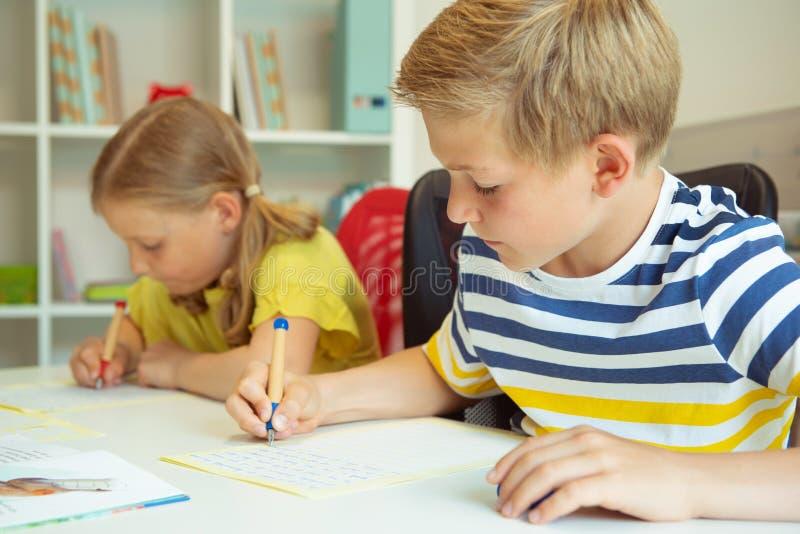 逗人喜爱的学童是回来了到学校和学会在桌上 图库摄影
