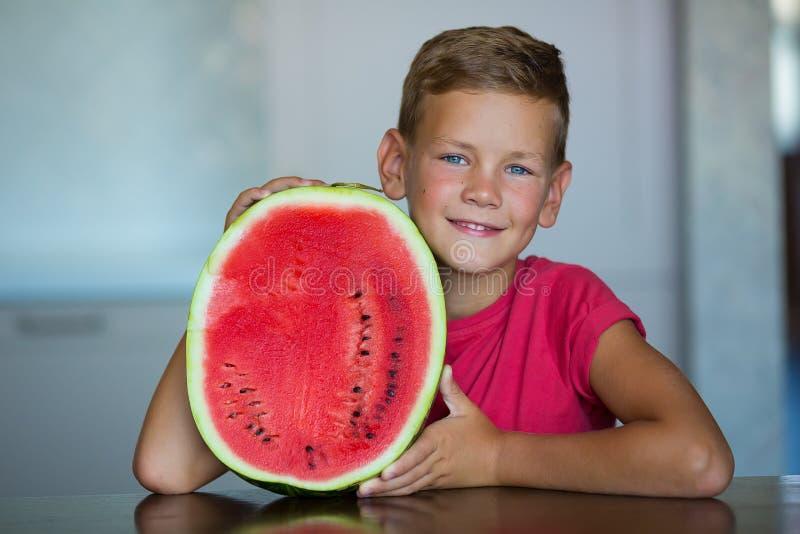 逗人喜爱的孩子享用穿有切片的夏天水多的莓果西瓜英俊的蓝眼睛男孩红色T恤杉西瓜被隔绝  库存图片