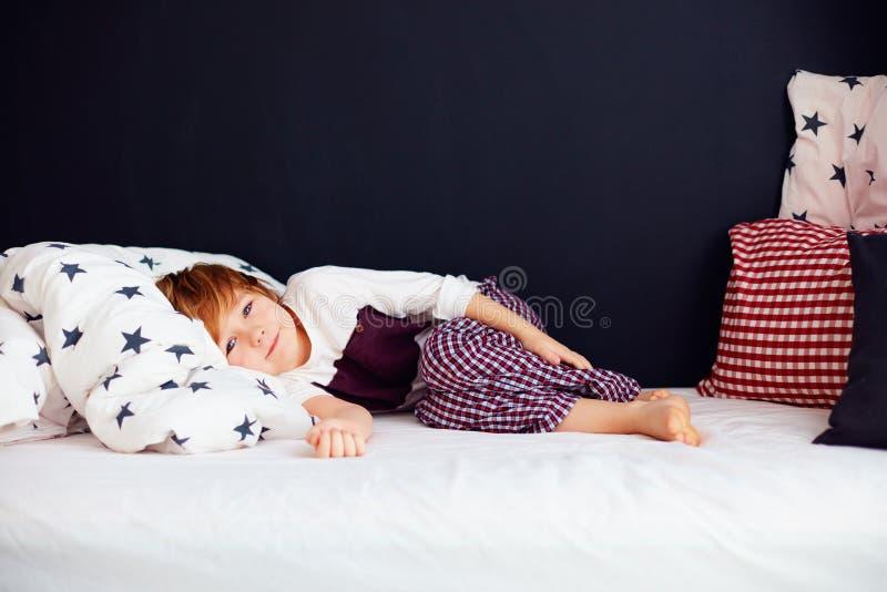逗人喜爱的孩子佩带的睡衣,在床上的轻松的男孩 免版税库存图片