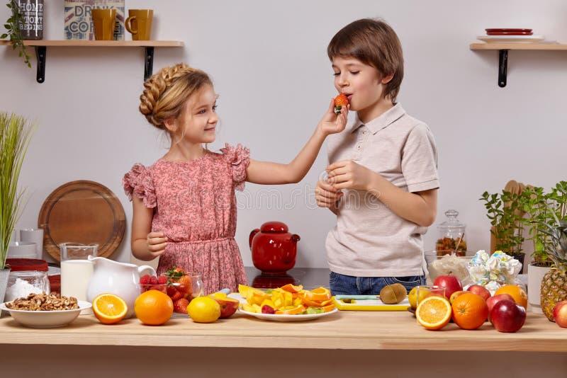 逗人喜爱的孩子在厨房里一起烹调对有架子的白色墙壁对此 免版税图库摄影
