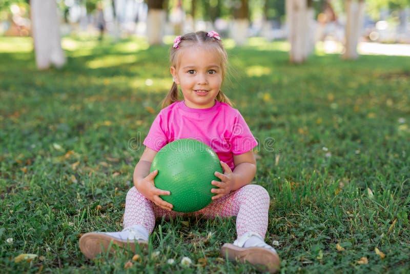 逗人喜爱的孩子女婴坐草在公园,使用与绿色球和微笑 免版税库存照片