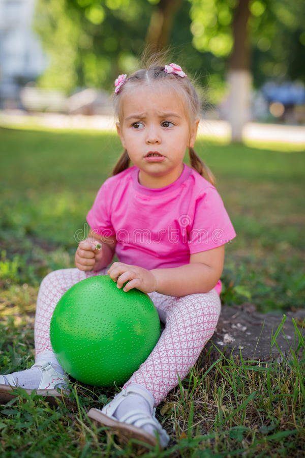 逗人喜爱的孩子女婴坐草在公园,使用与绿色球和微笑 免版税库存图片