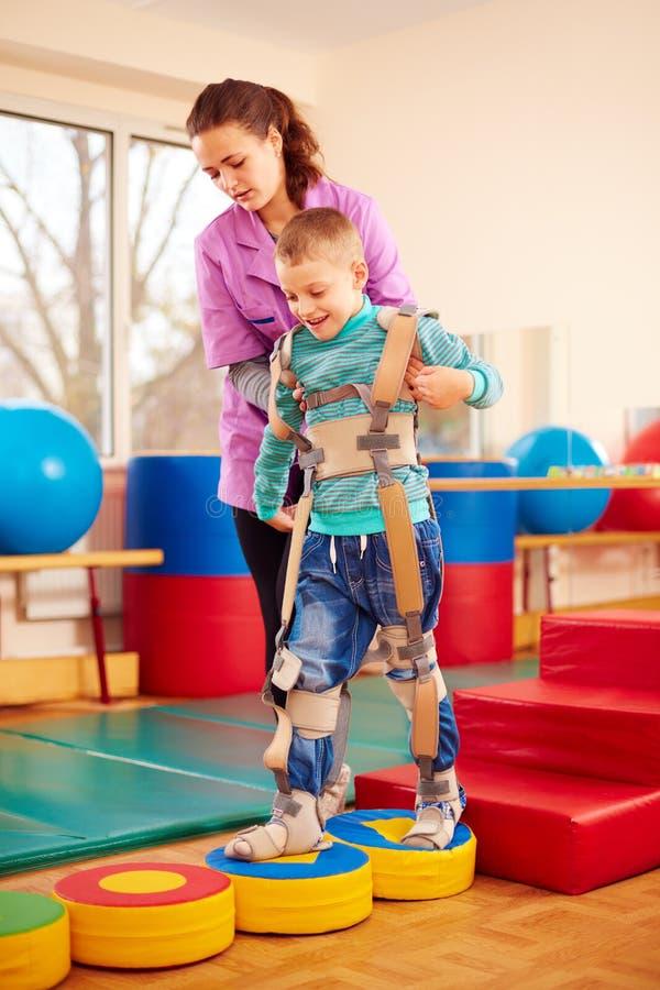逗人喜爱的孩子有物理肌肉与骨骼的疗法在康复中心 免版税图库摄影
