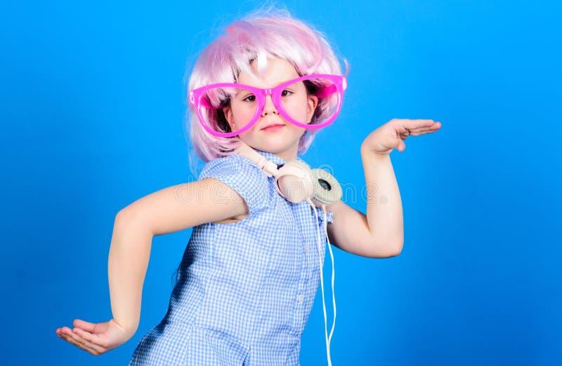 逗人喜爱的孩子有耳机蓝色背景 小女孩耳机桃红色假发跳舞 使用技术的孩子为乐趣 现代 库存图片