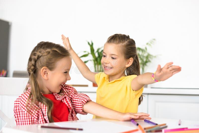 逗人喜爱的孩子画象在与铅笔和纸的桌上画的 免版税图库摄影