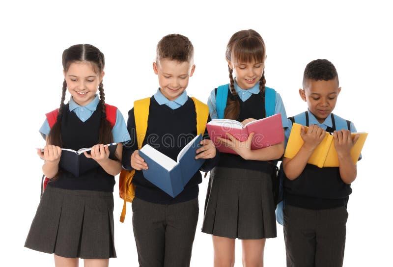 逗人喜爱的孩子画象校服的有在白色的书的 免版税库存照片