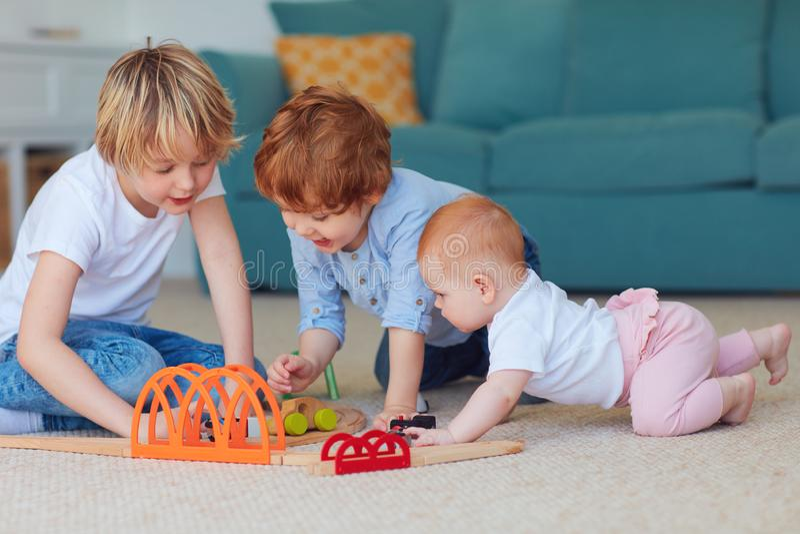 逗人喜爱的孩子,一起演奏玩具的兄弟姐妹在地毯在家 免版税库存照片
