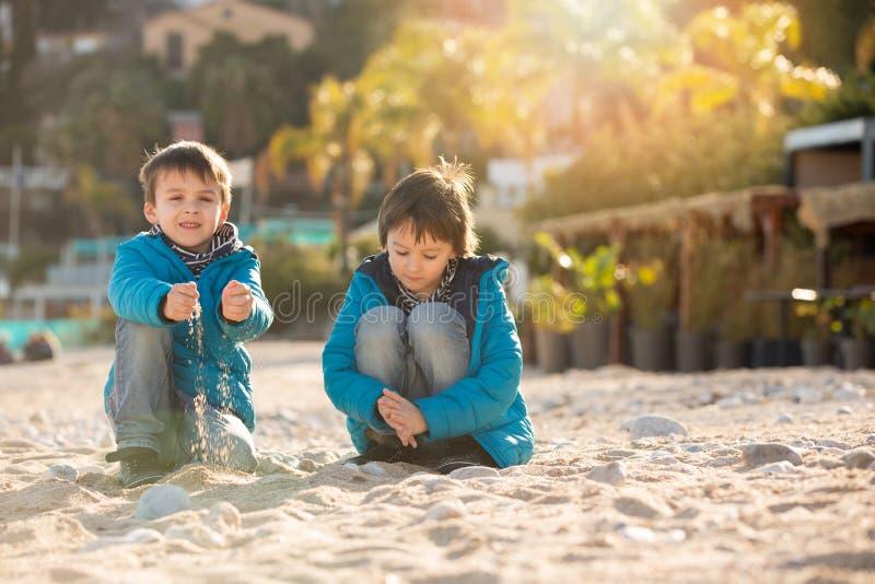 逗人喜爱的孩子,男孩兄弟,使用在与沙子pebb的海滩 库存图片