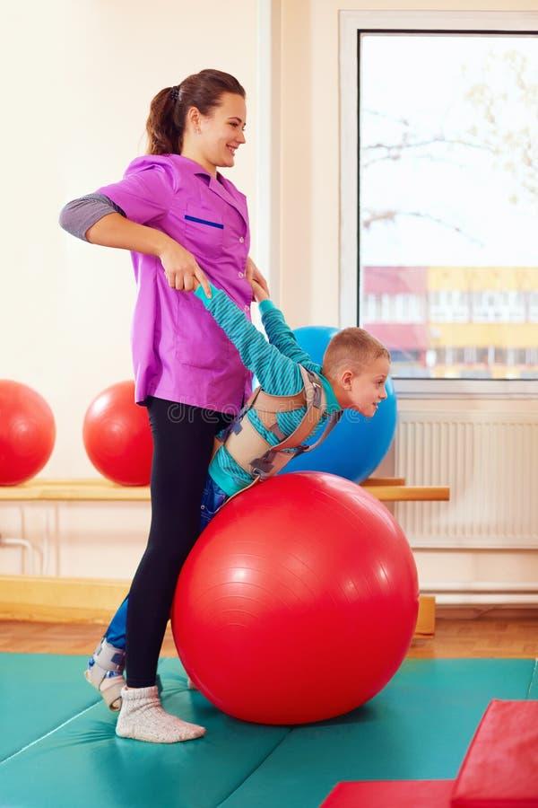 逗人喜爱的孩子以伤残有肌肉与骨骼的疗法通过做锻炼在身体在适合球的定象传送带 免版税图库摄影