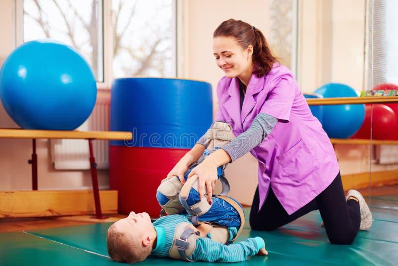 逗人喜爱的孩子以伤残有肌肉与骨骼的疗法通过做锻炼在身体定象传送带 免版税库存图片