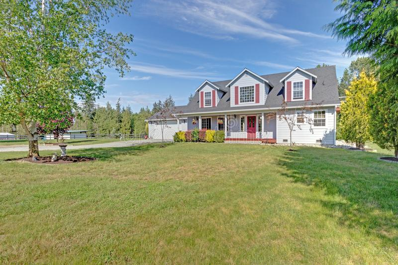逗人喜爱的家外部与红色快门在一个夏日 库存照片