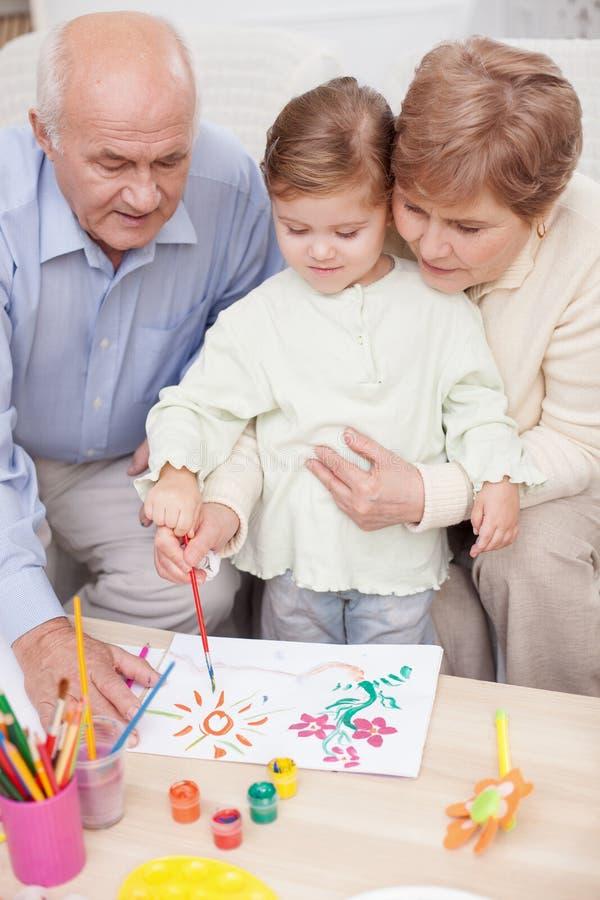 逗人喜爱的家庭在家一起绘 免版税库存照片