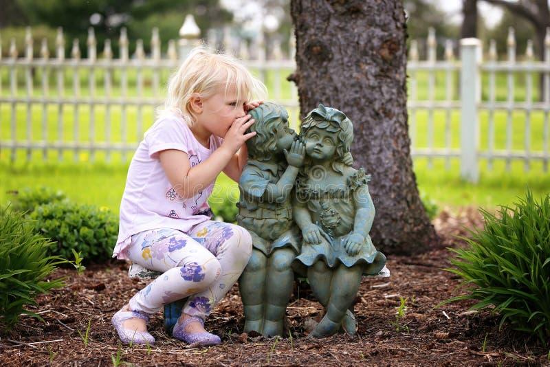 逗人喜爱的对小庭院雕象朋友的女孩耳语的秘密 图库摄影