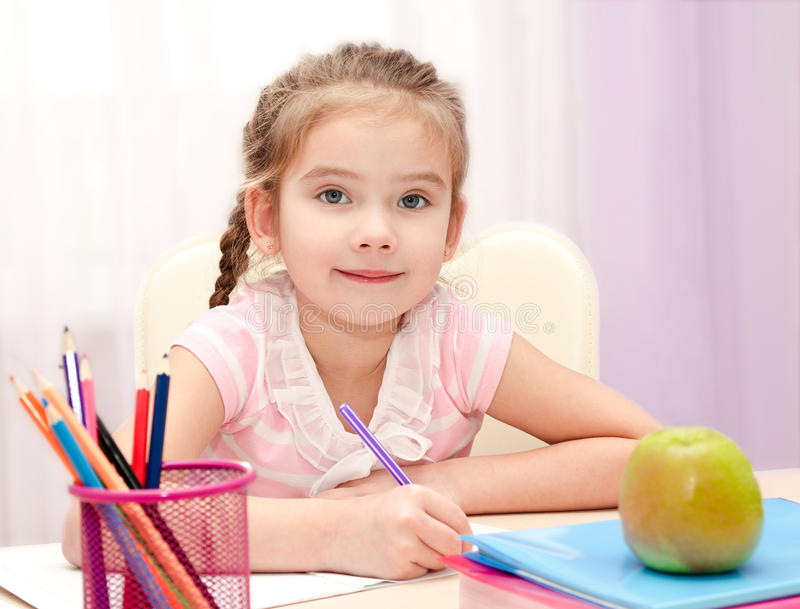 逗人喜爱的小女孩书写在书桌 免版税图库摄影