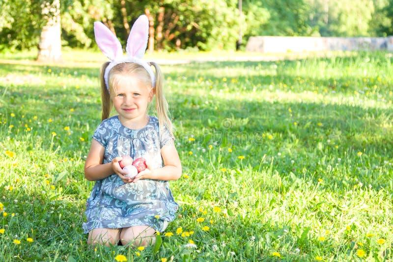逗人喜爱的小女孩佩带的兔宝宝耳朵在复活节天 坐草和拿着被绘的复活节彩蛋的女孩 免版税库存图片