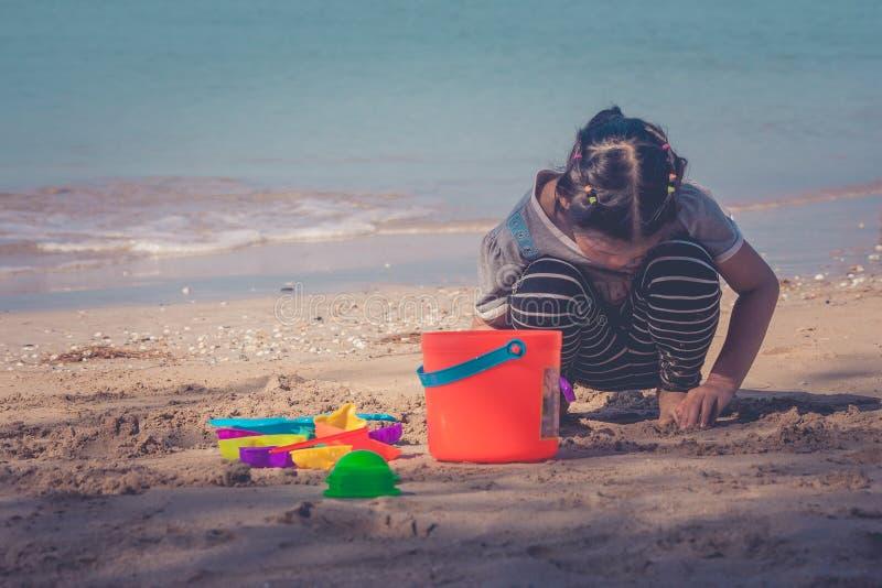 逗人喜爱的小女孩使用和享用与五颜六色的海滩玩具的或在沙子的儿童玩具在背景中靠岸有海景视图 库存照片