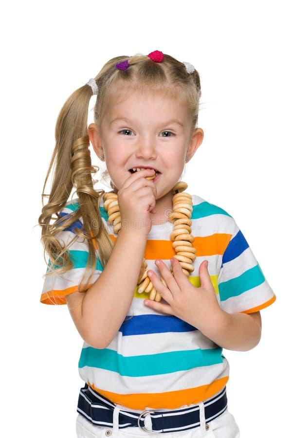 逗人喜爱的小女孩吃百吉卷 库存图片