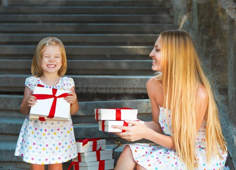 逗人喜爱的小女孩和她的母亲藏品礼物 免版税库存图片