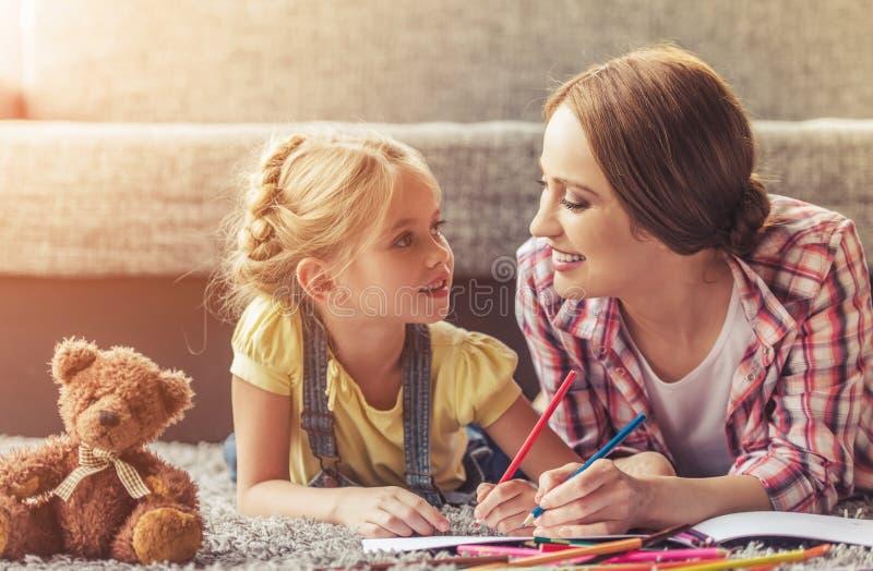 逗人喜爱的小女孩和她美丽的母亲图画 免版税图库摄影