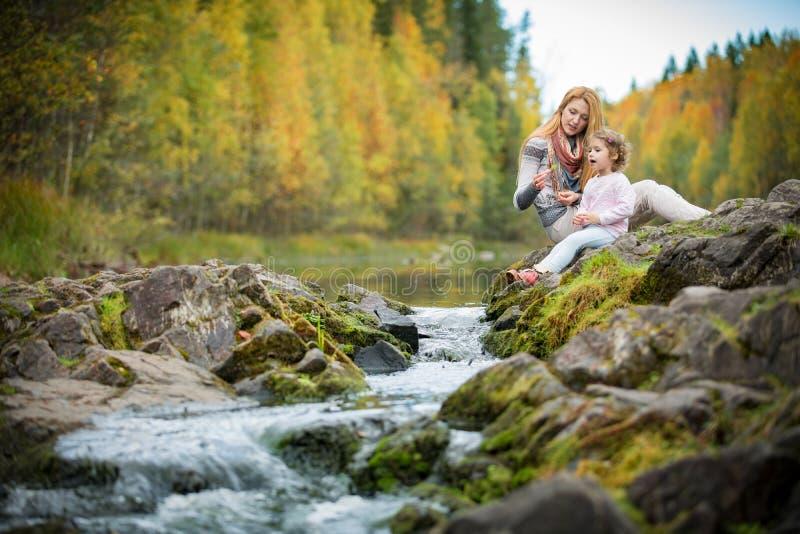 逗人喜爱的小女孩和母亲坐一个岩石在秋天森林里在小河 免版税库存照片