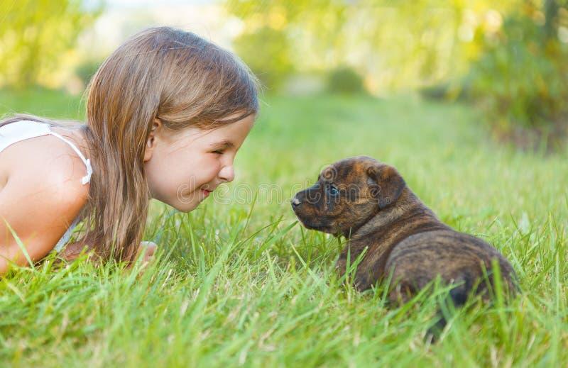 逗人喜爱的小女孩和狗小狗 免版税库存照片