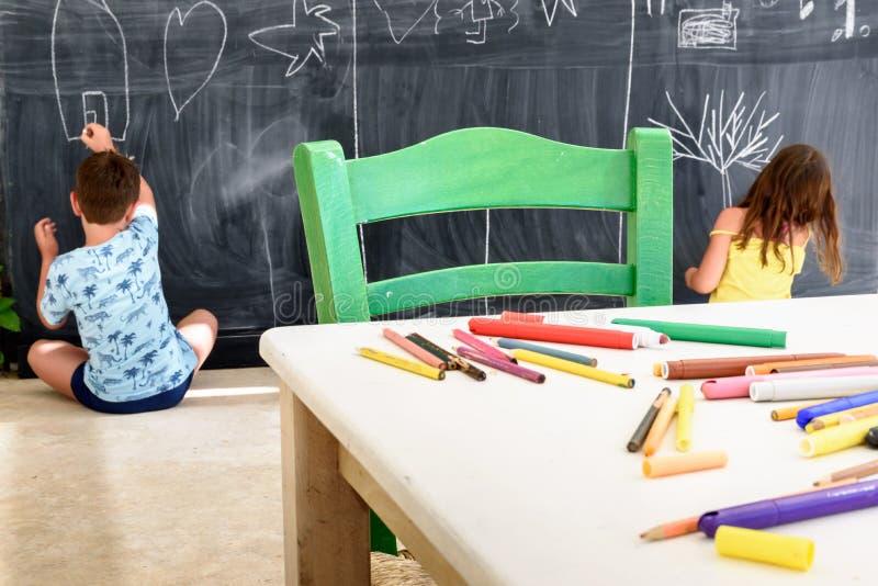 逗人喜爱的小女孩和男孩图画和绘画在幼儿园 创造性的活动孩子俱乐部 免版税图库摄影