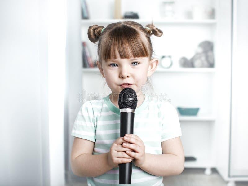 逗人喜爱的小女孩唱歌卡拉OK演唱在家 库存照片
