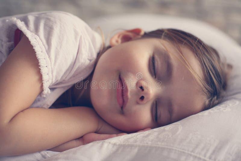 逗人喜爱的小女孩在床上 免版税库存图片