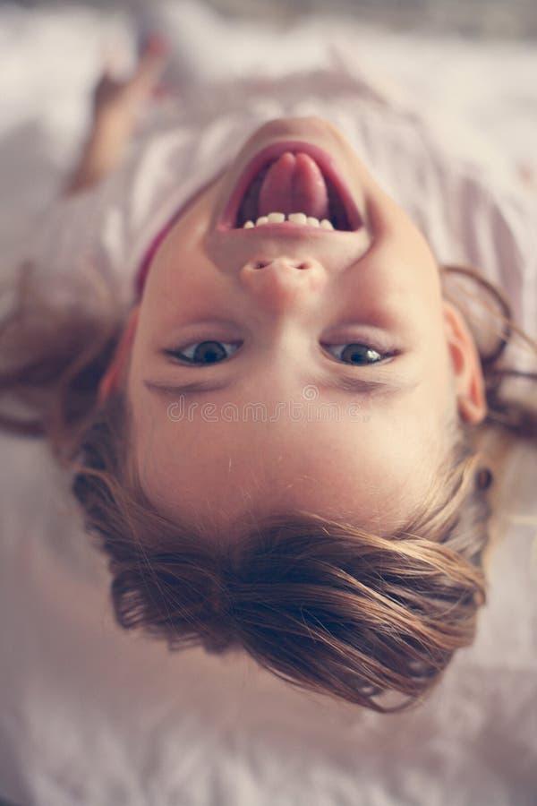逗人喜爱的小女孩在床上 免版税库存照片