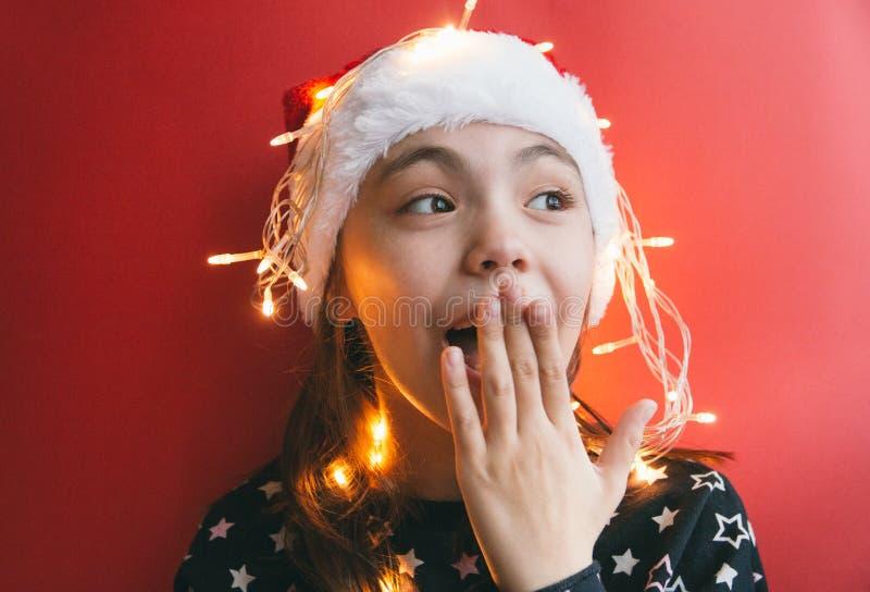逗人喜爱的小女孩在有诗歌选的圣诞老人帽子在红色背景 库存照片