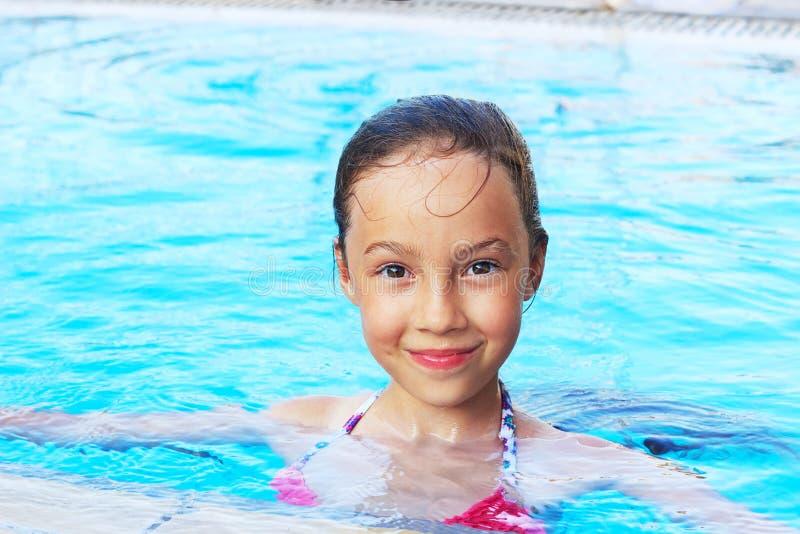 逗人喜爱的小女孩在游泳池微笑着 夏天,假期, 图库摄影