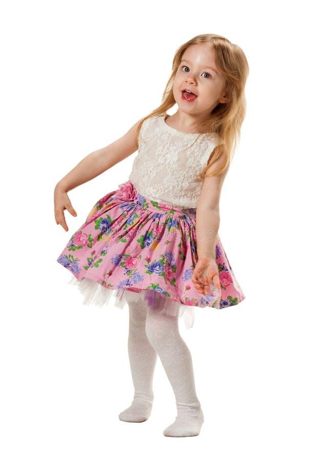 逗人喜爱的小女孩在白色背景唱歌曲和笑隔绝了 免版税库存图片