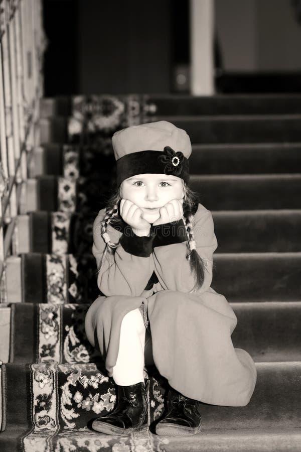 逗人喜爱的小女孩在老房子里面的减速火箭式外套穿戴了 库存照片
