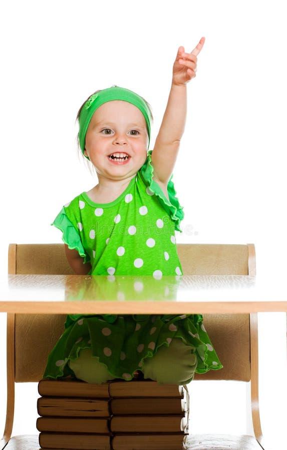 逗人喜爱的小女孩在表坐书 免版税库存照片